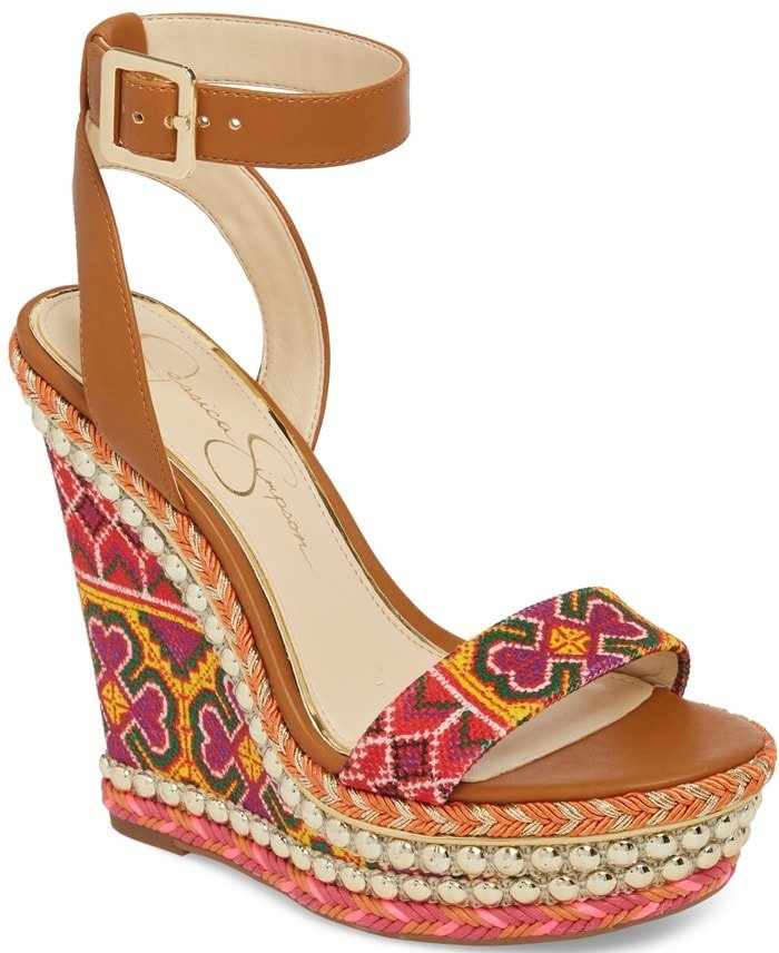 A joyful celebration of colors, patterns and textures, this towering wedge sandal from Jessica Simpson is clad in sunny cross-stitching and framed in braiding and gleaming studs