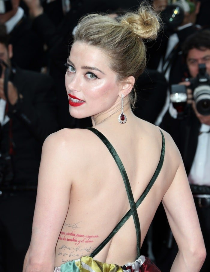 "Amber Heard has a quote from the Chilean poet Pablo Neruda tattooed in red ink on her left side. The Spanish words ""te amo como se aman ciertas cosas oscuras, secretamente, entre la sombra y el alma"" translate to ""I love you as certain dark things are to be loved, in secret, between the shadow and the soul"""