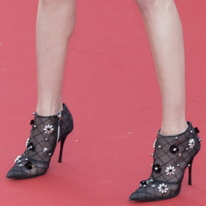 Amber Heard showing off her black fabric ankle boots with rhinestone appliques, pearls and micro-sequins, metallic leather trims, side zip closing