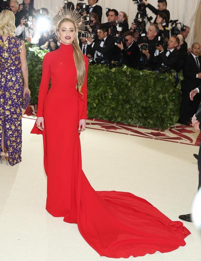 Amber Heard in a regal red long-sleeve Carolina Herrera gown
