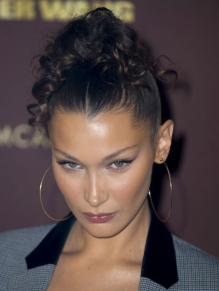 Bella Hadid with a curly top ponytail and gold hoop earrings.