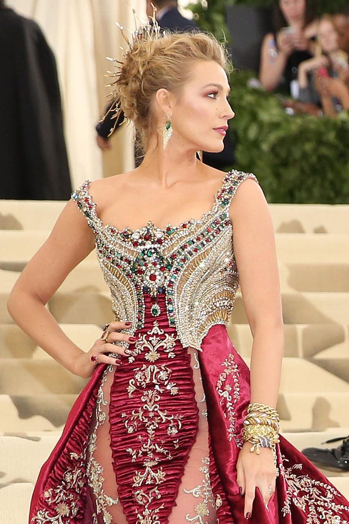 Blake Lively wearing over $2 million worth of Lorraine Schwartz jewelry, including a halo, Colombian-emerald-an-diamond earrings, gold bracelets, and her own engagement ring.