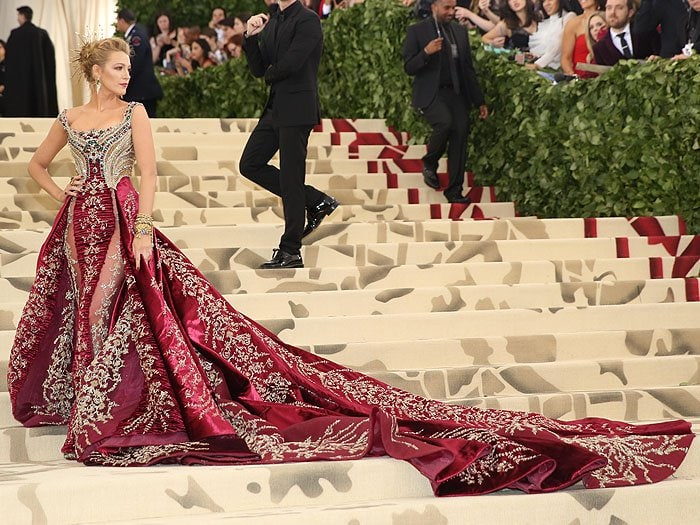 Blake Lively posing in her Atelier Versace wine red and gold gown at the 2018 Met Gala.