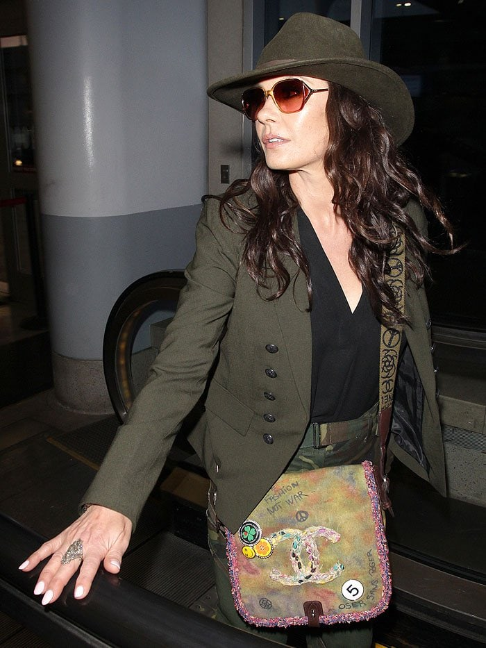 Catherine Zeta-Jones wearing a dark-green fedora, a matching jacket, and camo pants with a Chanel graffiti bag.
