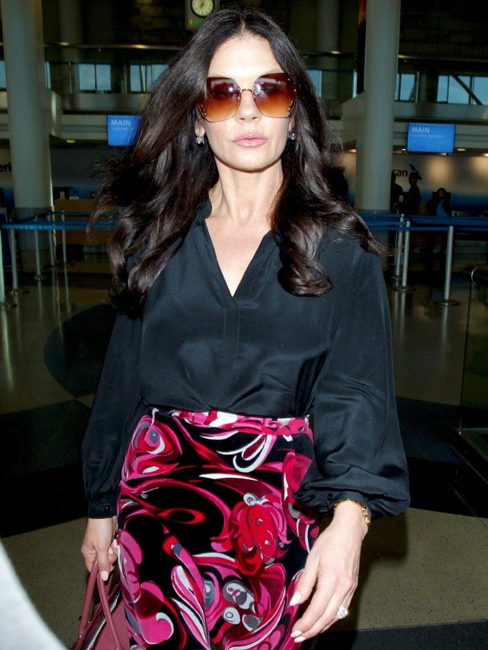 Catherine Zeta-Jones with flowing black hair and brown oversized sunglasses