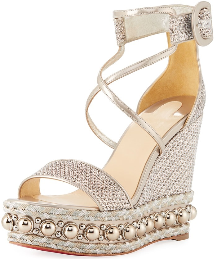 This pair features a self-covered platform wedge embellished with raffia, specchio leather, and light goldtone dome studs