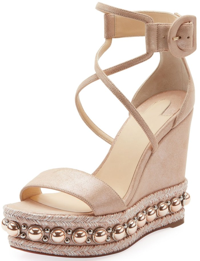Polished dome studs and metallic braiding trace the sole of an elegantly tall platform wedge secured by curvy straps and a buckled ankle cuff