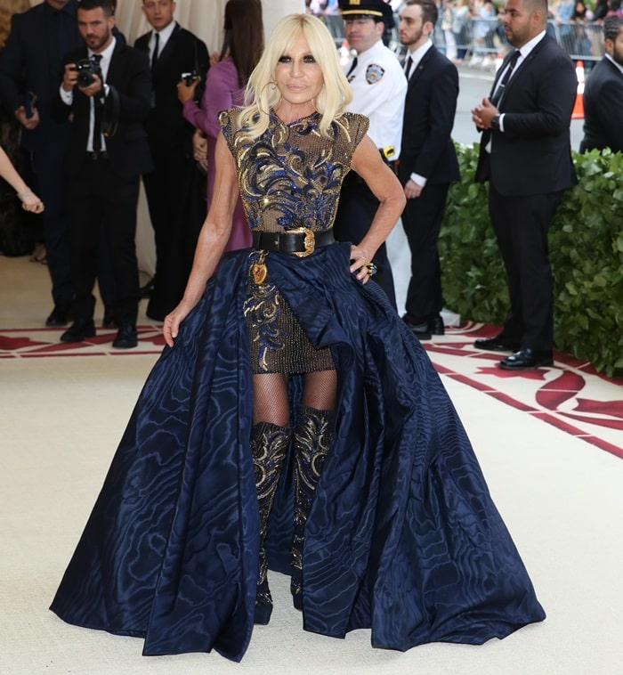 Donatella Versace in an embroidered mini dress styled with matching knee boots and a black belt
