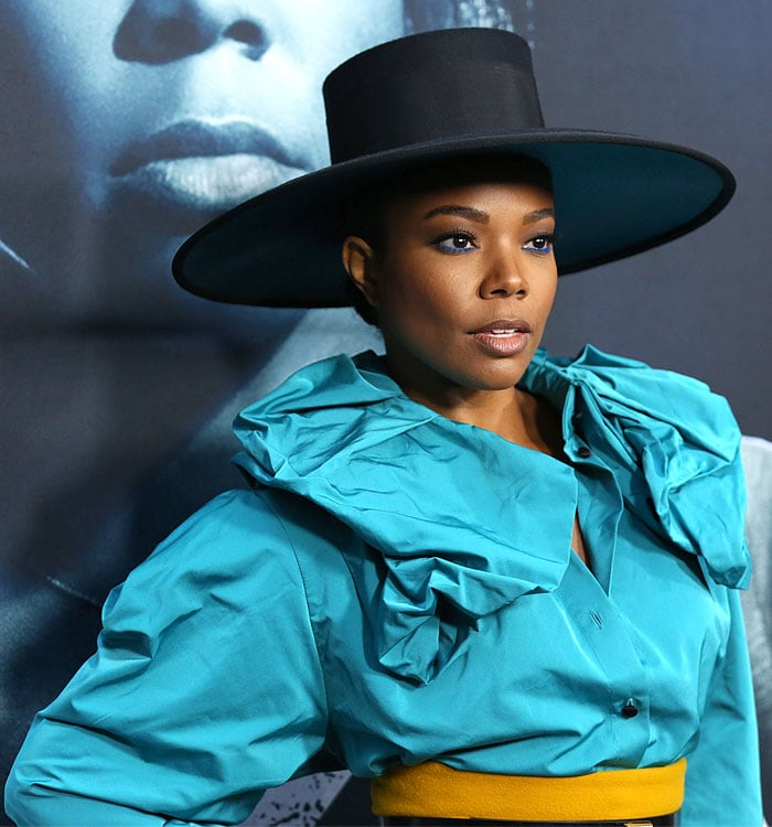 Gabrielle Union wearing blue eyeliner, a top hat, a blue ruffled blouse, and yellow pants.