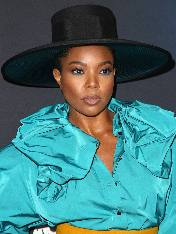 Gabrielle Union in a Marc Jacobs top hat and blue ruffled blouse.
