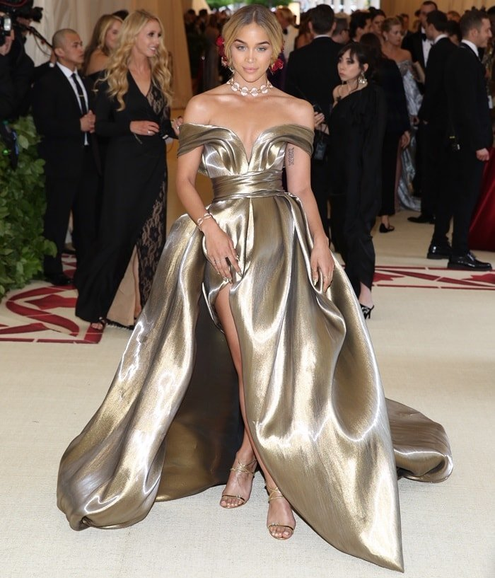 Jasmine Sanders wearing a customgolden gown featuring an off-the-shoulder neckline and thigh-high split