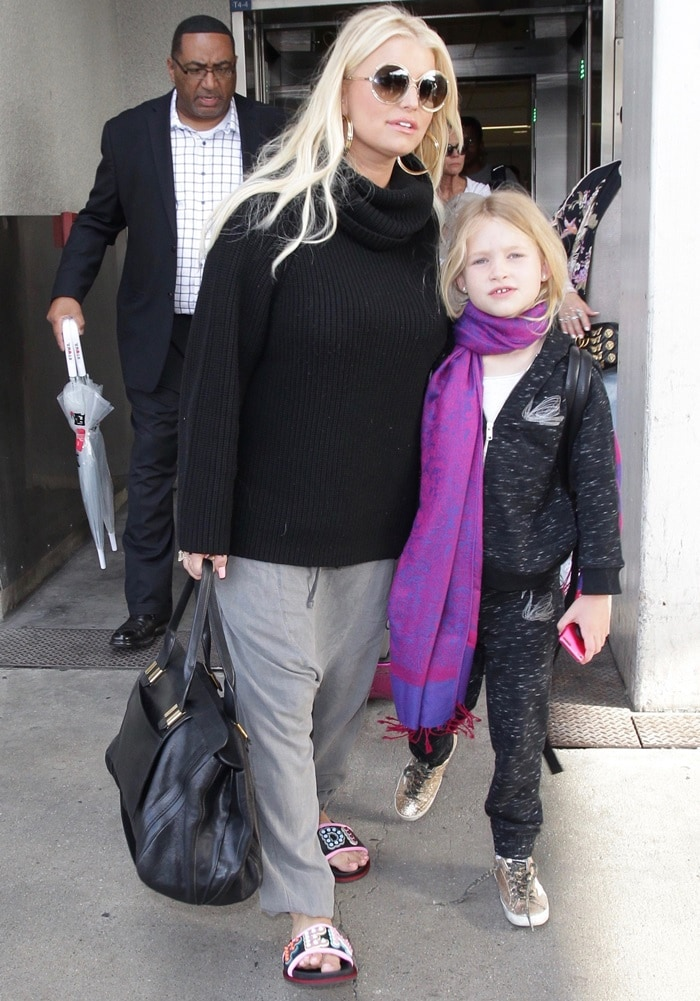 Jessica Simpson in sweatpants, a comfy black sweater, and studded logo slide sandals from Fendi