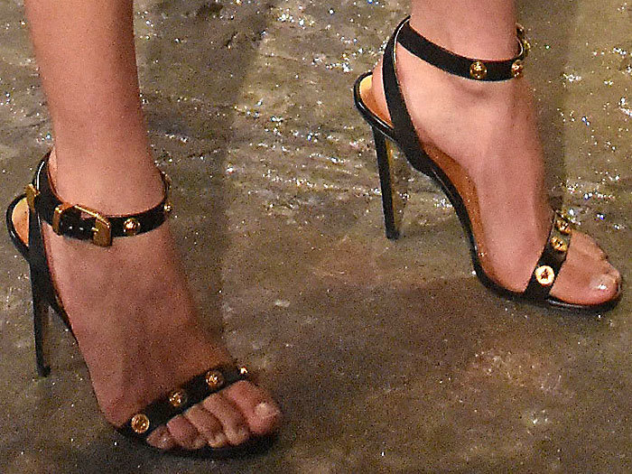 Details of the Versace Medusa-medallion ankle-strap sandals on Kaia Gerber.
