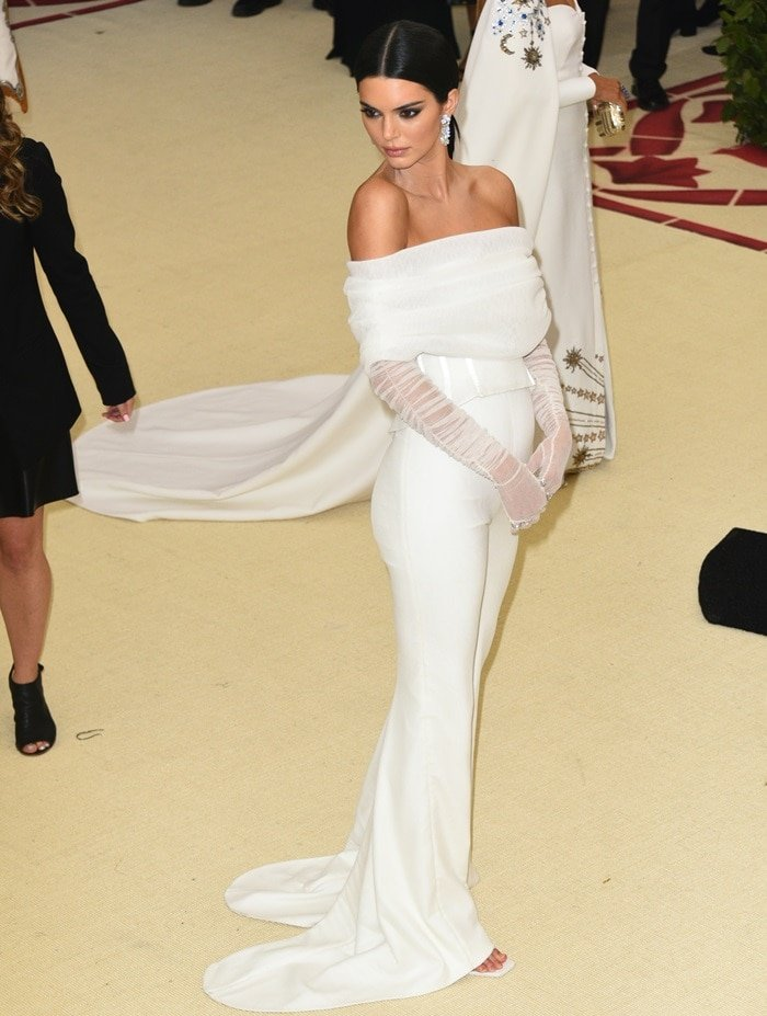 Kendall Jenner in awhite bustier top with matching sheer gloves