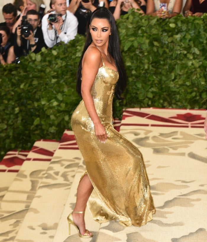 Kim Kardashian showing off hergolden metallic ankle-strap sandals