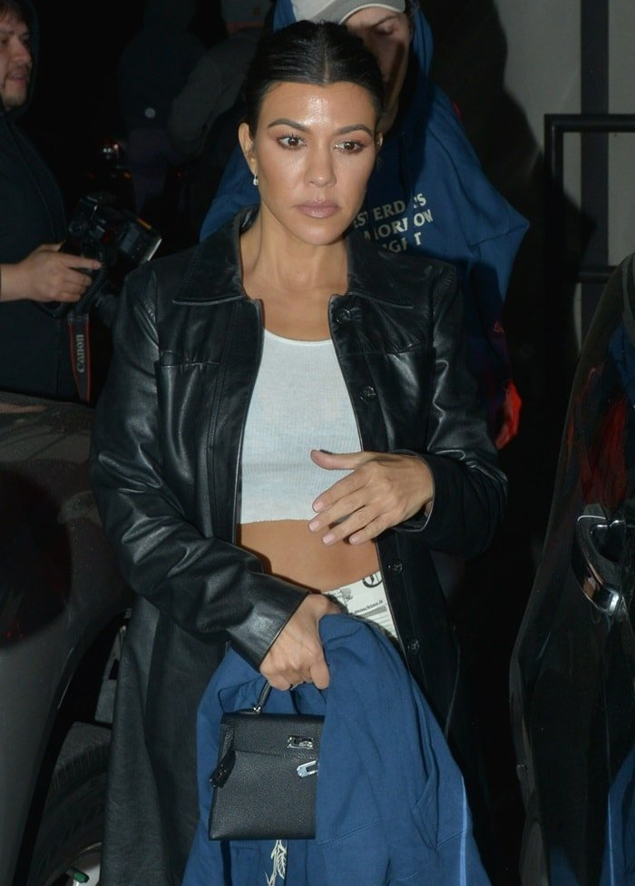 Kourtney Kardashian in a white crop top paired with a black leather coat