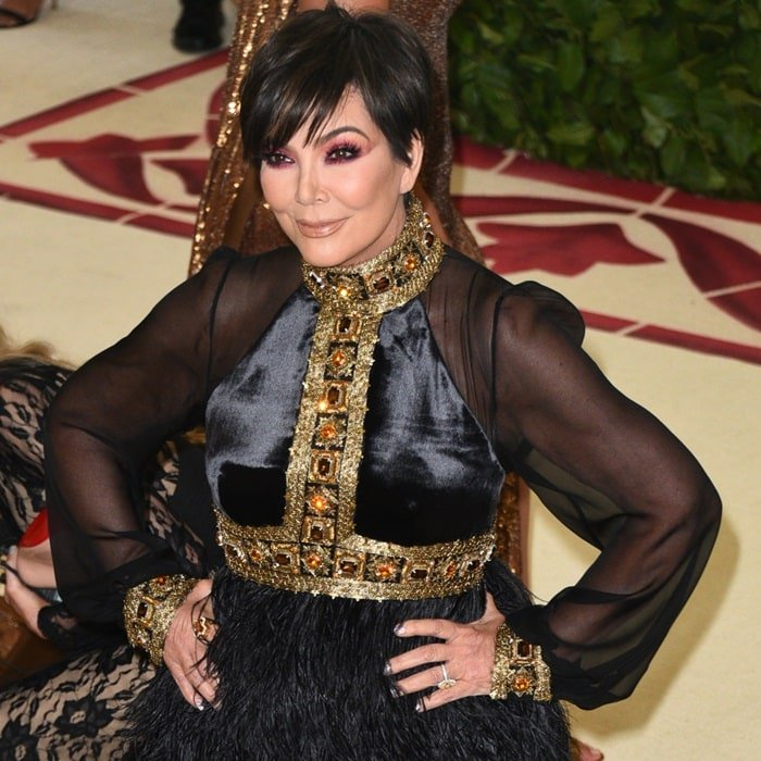 Kris Jenner in a black long-sleeve gown featuring gold and burgundy jeweled embellishments and a feather-embellished skirt
