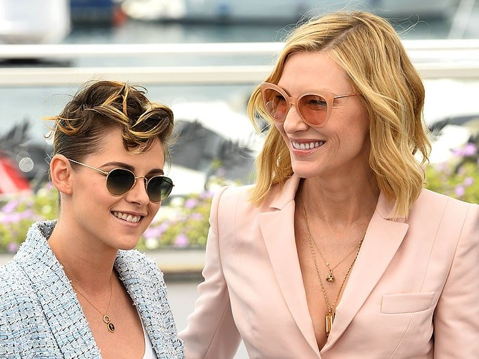 Kristen Stewart and Cate Blanchett wearing sunglasses and pantsuits.