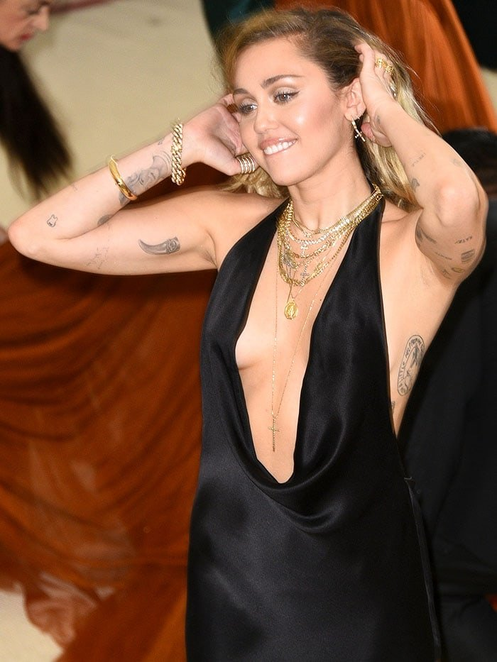 Miley Cyrus showing her tattoos and layered gold cross and chain necklaces.