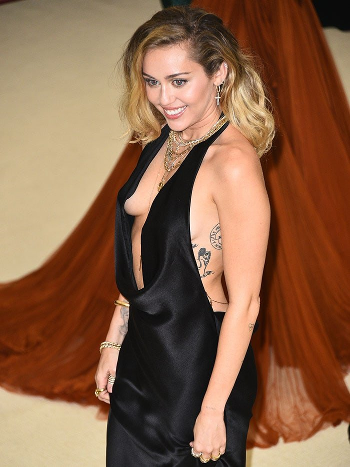 Miley Cyrus flashing underboob in a Stella McCartney gown with a plunging neckline.