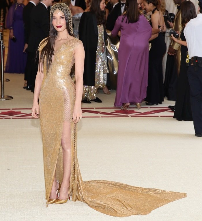 Olivia Munn shimmered ina sleeveless gold floor length dress from the H&M Conscious Collection