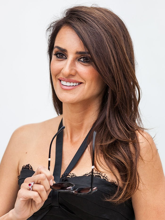Penelope Cruz taking of her sunglasses in a black Chanel dress.