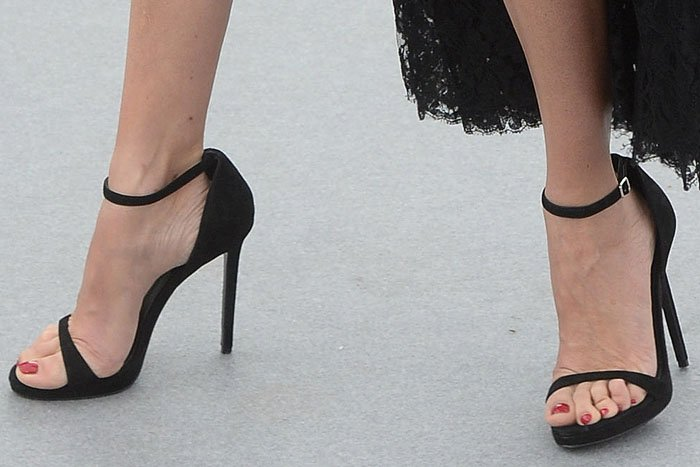 Penelope Cruz's toes all squashed up together in Versace black-suede ankle-strap sandals.