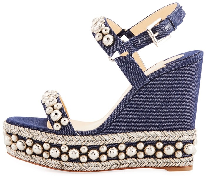 Indigo denim adds a laid-back touch to a wedge sandal rich with textures, shining studs and shimmering braided trim