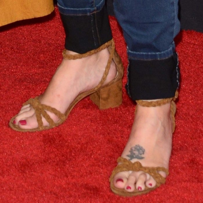 Roseanne Barr showing off a rose foot tattoo in a pair of brown sandals