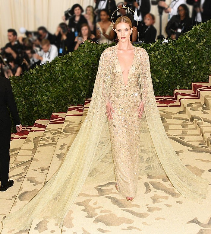 Rosie Huntington-Whiteley in a Ralph Lauren Collection gown and gold Jimmy Choo sandals.