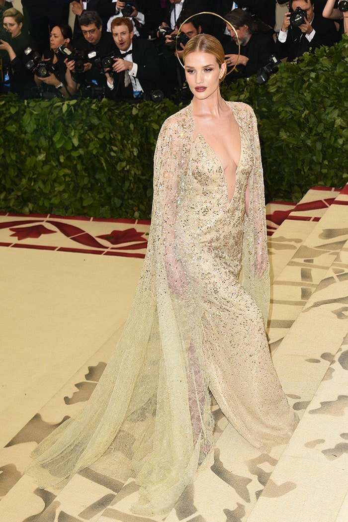Rosie Huntington-Whiteley in a Ralph Lauren Collection gown, gold halo, and gold Jimmy Choo 'Kaylee' sandals.