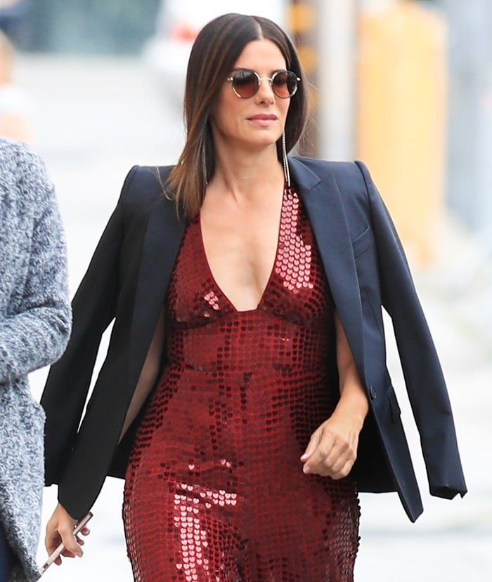 Sandra Bullockwore her hair in a sleek middle part and accessorized withround Cartier sunglasses and dangling earrings