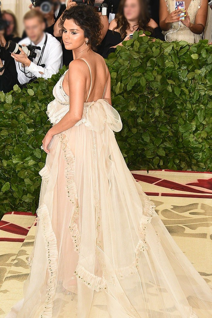 Back view of Selena Gomez's Coach Met Gala matronly gown with a proverb-embroidered ribbon down the back.