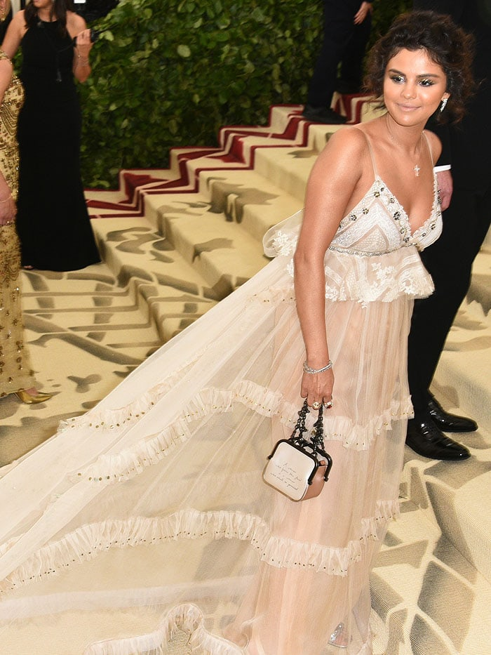 Selena Gomez's custom Coach gown and Coach 'Kisslock Frame' handbag at the 2018 Met Gala.