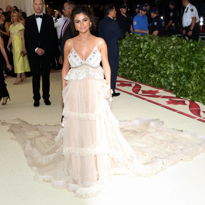 Selena Gomez in a custom Coach vintage silk-gauze gown with a long train and silver custom Coach ankle-strap sandals.