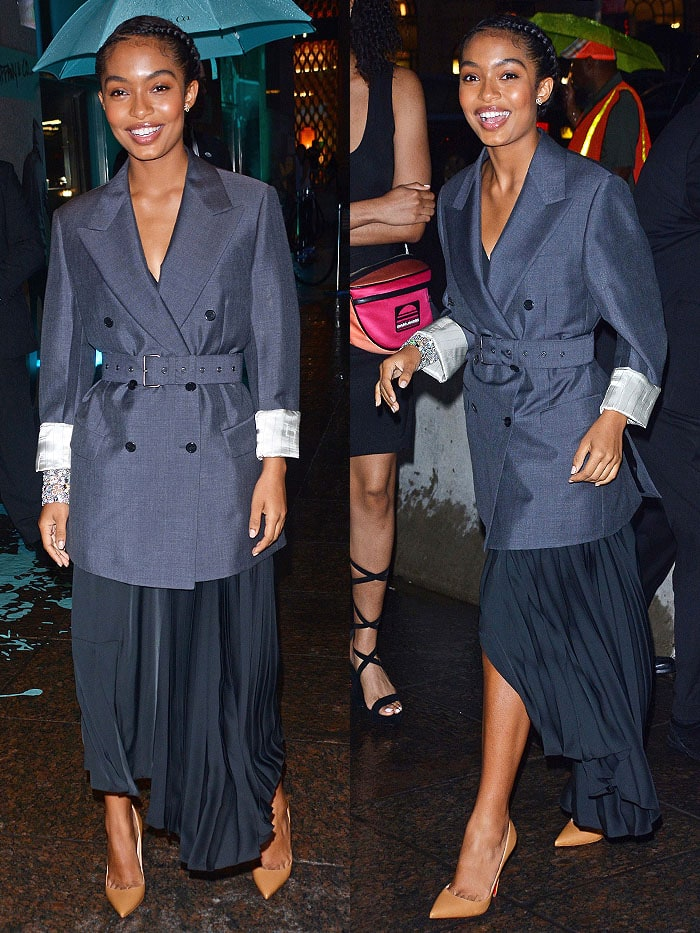 Yara Shahidi in a black Prada half-pleated dress, belted gray double-breasted jacket, and Christian Louboutin 'So Kate' pumps.