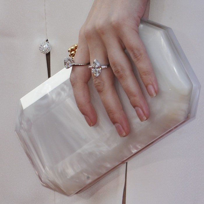 Anna Kendrick showing off her rings and small 'Perry' clutch from Tyler Ellis