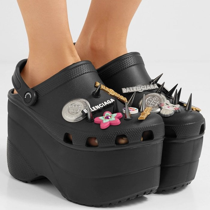 Made from black rubber, this lightweight pair is set on a towering foam platform and personalized with playful rubber charms, spikes and logo-embossed pins.