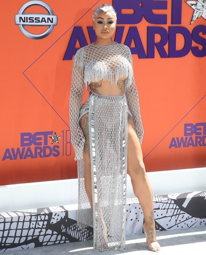 Blac Chyna showing underboob in a chainmail slitted skirt and crop top from New York-based designer Laurel DeWitt
