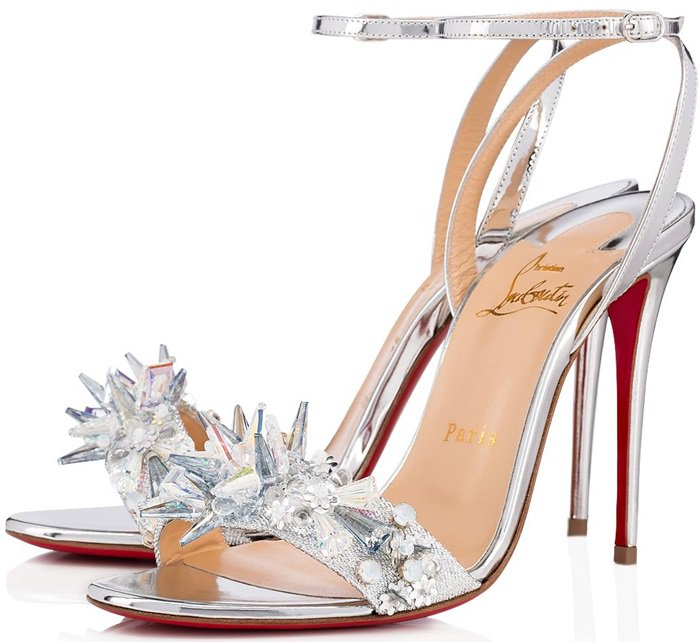 A starburst of glinting crystals, glimmering stones and sequins shines at the vamp of a silvery ankle strap sandal set on a slender stiletto heel