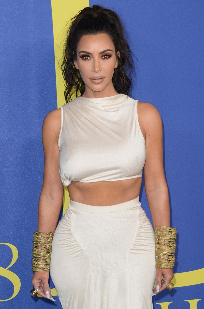 Kim Kardashian in a curve-hugging white crop top and a flowy floor-length skirt by Rick Owens