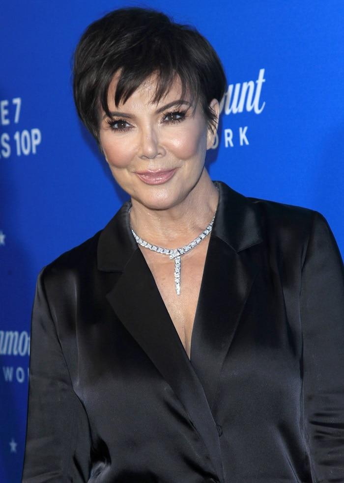 Kris Jenner wearing a sparkling diamond necklace anda black silk blazer mini-dress