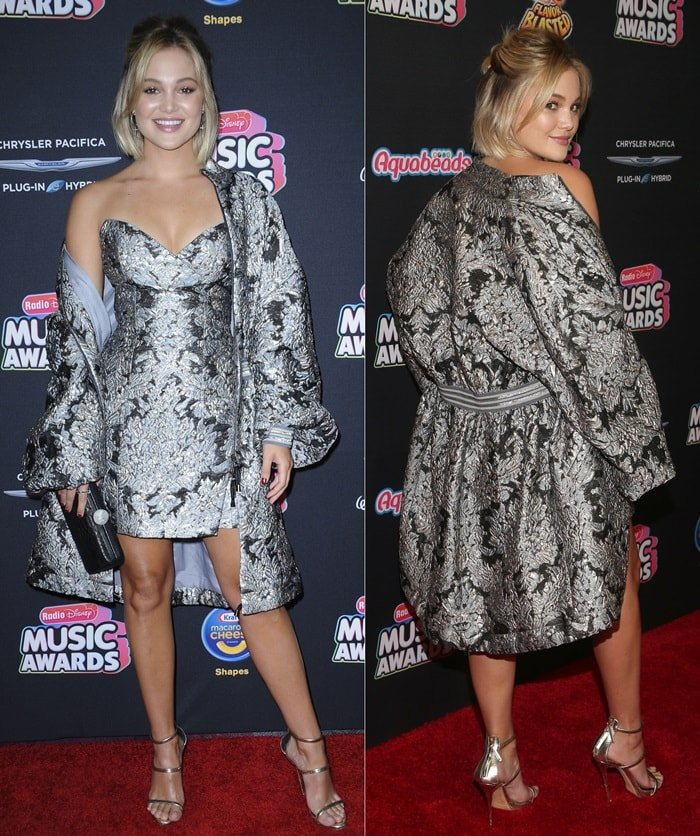 Olivia Holt in a brocade strapless wrap mini dress styled with a matching jacket from Israeli fashion house Galia Lahav at the 2018 Radio Disney Music Awards held in Los Angeles on June 22, 2018