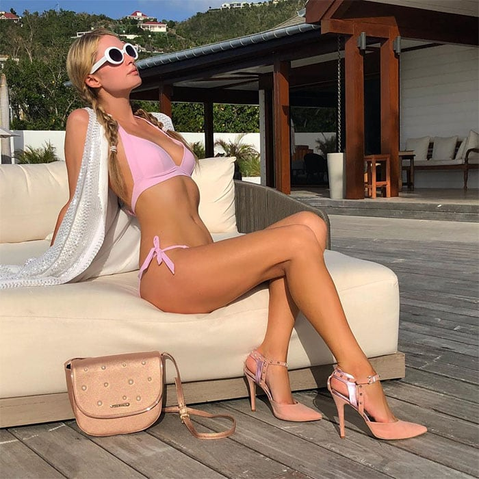 Paris Hilton wearing a pink bikini with pink ankle-strap pumps and a pink handbag.