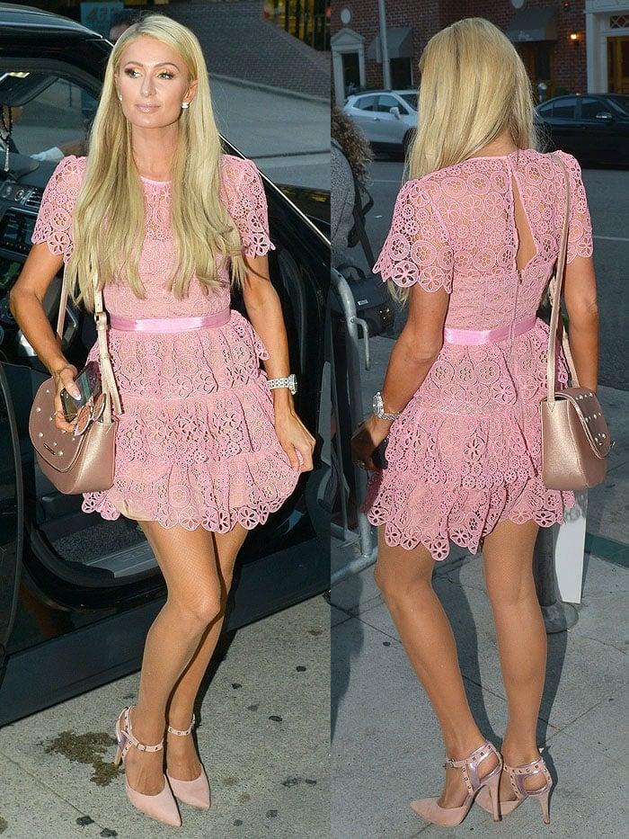 Paris Hilton accessorizing a pink Self-Portrait dress with a Paris Hilton shoulder bag and ankle-strap pumps.