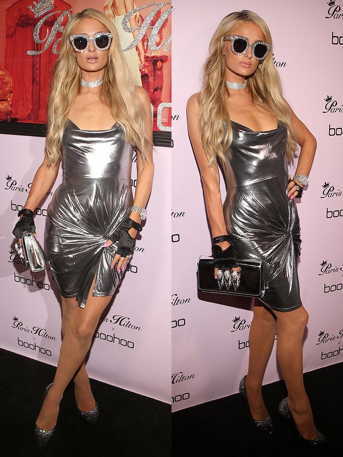 "Paris Hilton wearing a Paris Hilton x Boohoo silver wrap dress, Philipp Plein crystal pumps, and a Philipp Plein ""It Is for You"" clutch."