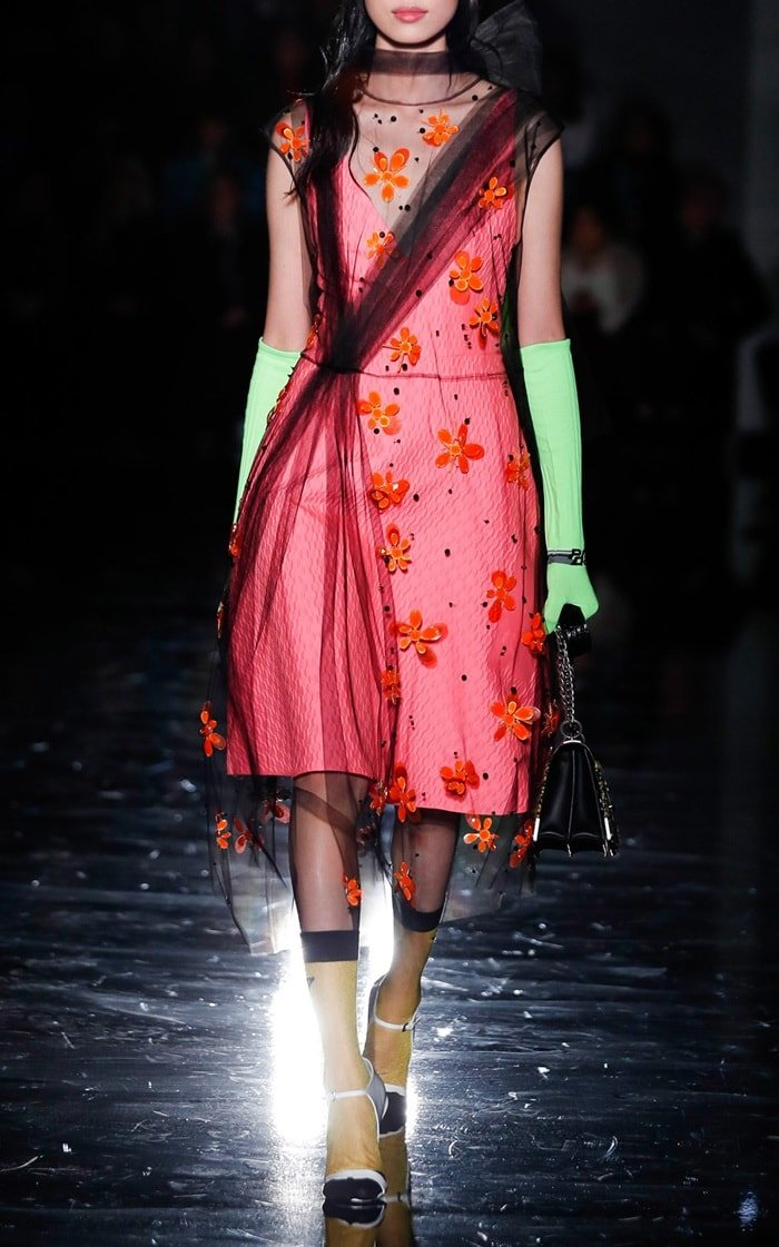 Model wearing Prada gloves featuring a two tone design and feature s long silhouette.