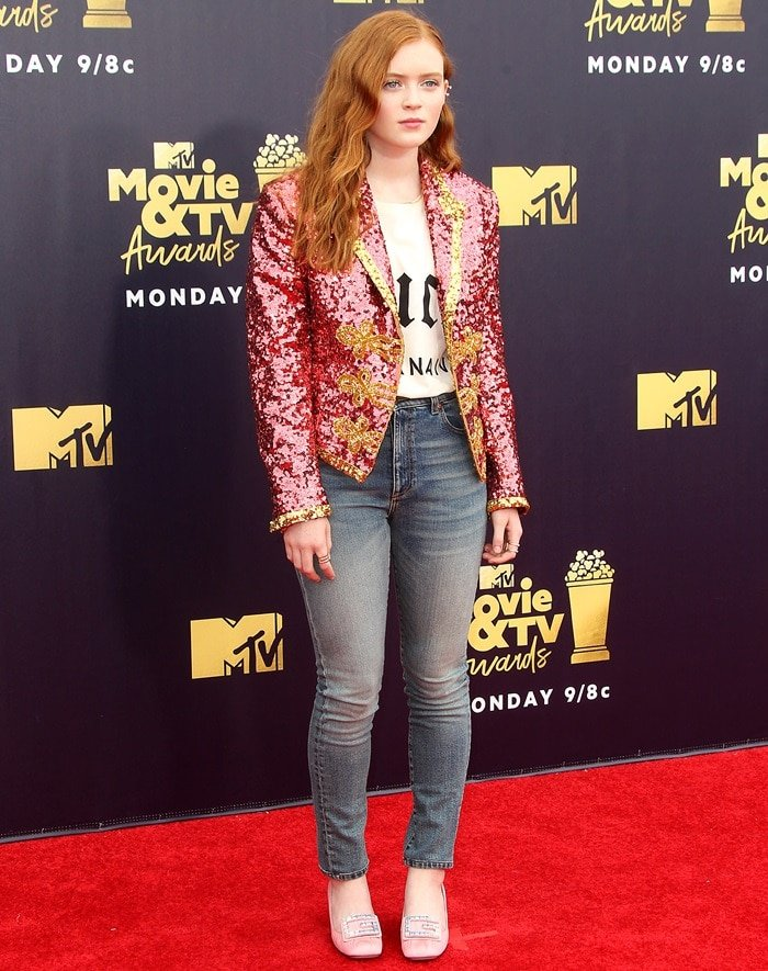 "Sadie Sink rocking a a ""Guccy Internaive XXV"" cotton T-shirt and classic blue skinny jeans"