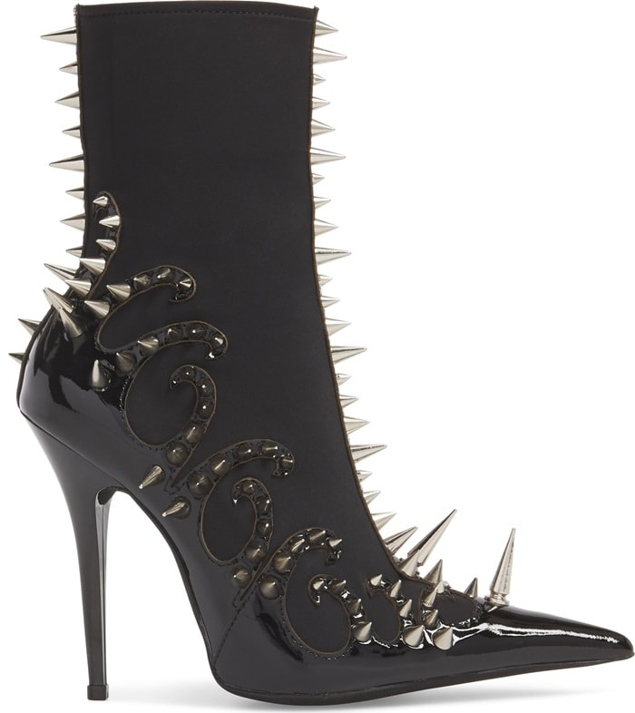 Fiery tendrils bearing wicked spikes curl around the foot and run straight up the shaft of a stretchy, contour-hugging bootie spiked high on a tall stiletto