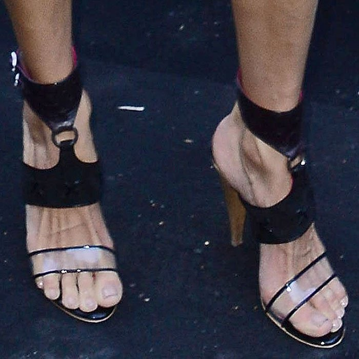Alessandra Ambrosio's bony feet in Peter Dundas Spring 2019 O-ring clear-strap ankle-cuff sandals.
